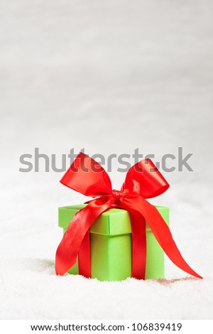 Green present with red ribbon over snow, over white - stock photo