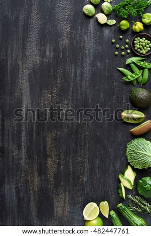 Green produce raw vegetables framing a distressed background, copy space for website poster magazine