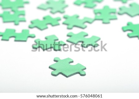 Green puzzle pieces on a white surface. Focus point on the piece in front.