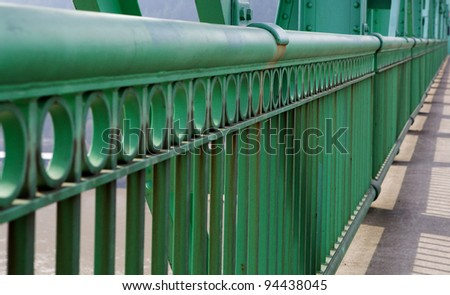 Green Railing in perspective on diminishing to soft focus - stock photo