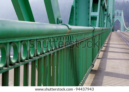 Green Railing perspective on St. Johns Bridge with view of one of the towers in soft background - stock photo