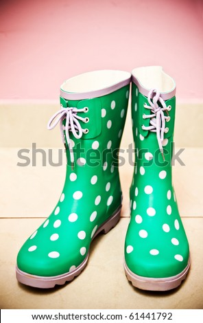 Green rain boots on pink background - stock photo
