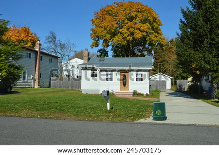 Green recycle reuse reduce trash can on front yard lawn of Suburban bungalow home sunny autumn clear blue sky day residential neighborhood USA - stock photo