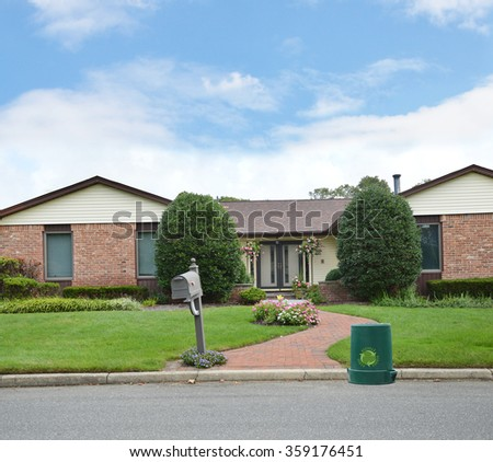 Green recycle, reuse, reduce, trash container Brick Walkway Mailbox to Suburban Brownstone brick Ranch Style Home Residential neighborhood Blue Sky clouds USA - stock photo