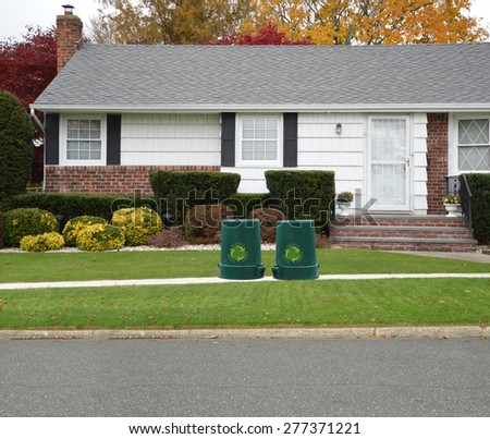 Green recycle, reuse, reduce, trash container Close up of Ranch style Home Autumn Day Residential Neighborhood USA - stock photo