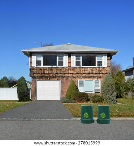 Green recycle, reuse, reduce, trash container Suburban American Square style home sunny autumn day clear blue sky residential neighborhood USA - stock photo