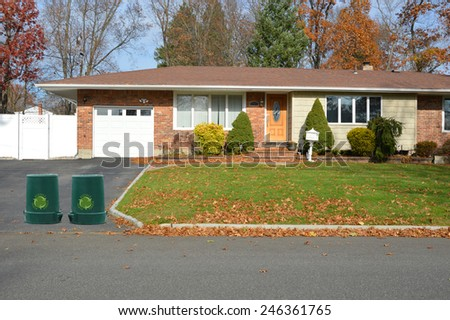 Green recycle, reuse, reduce, trash container suburban brick ranch style home white picket fence blacktop driveway autumn blue sky day residential neighborhood USA - stock photo