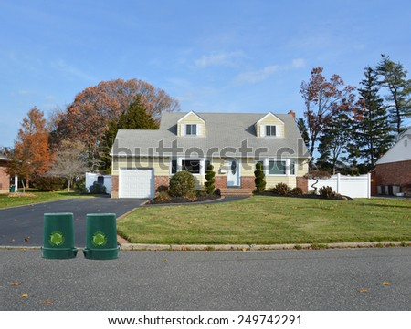 Green recycle, reuse, reduce, trash container suburban cape cod home autumn blue sky day residential neighborhood USA