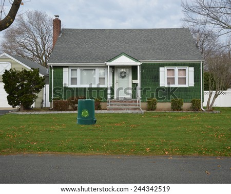 Green recycle trash container front yard lawn Suburban Bungalow Cape Cod style home autumn day residential neighborhood USA overcast sky - stock photo