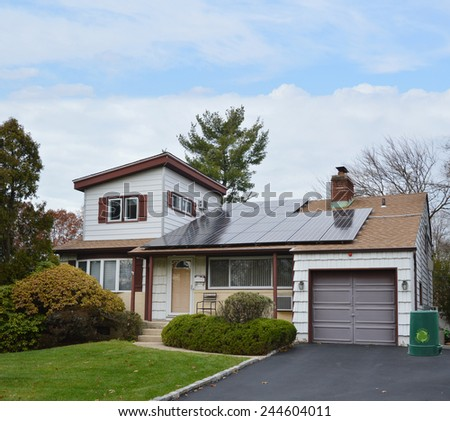 Green recycle trash container Suburban Ranch style home with solar panel on roof residential neighborhood USA blue sky clouds - stock photo
