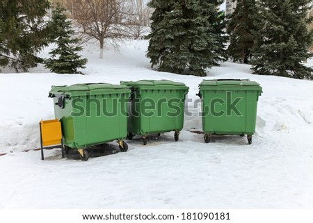 Green recycling containers in the winter park - stock photo