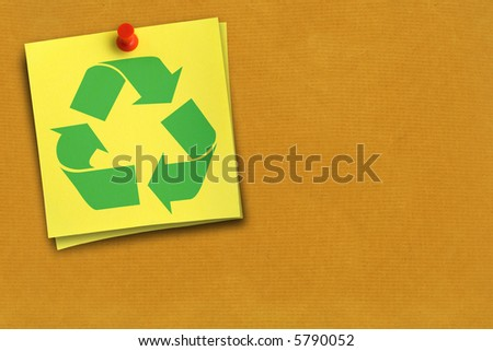 green recycling symbol on yellow note against cardboard background - stock photo