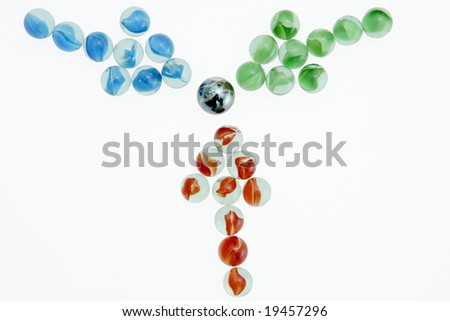 Green, Red, and Blue marbles arranged in arrows pointing towards the center. - stock photo