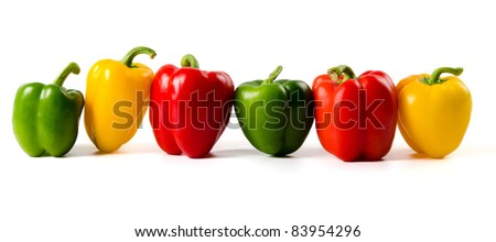 Green,red and yellow peppers lined up on a white background