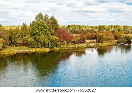 Green, red and yellow trees, the reflections of trees in the water, roofs of the house, the river against the blue cloudy sky - stock photo