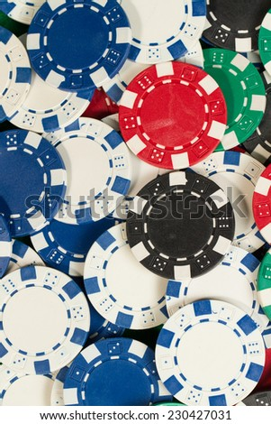 Green, red, blue, white and black Playing Poker Chips in a green background - stock photo