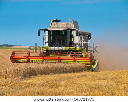 green red working harvesting combine in the field of wheat - stock photo