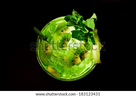 Green refreshing cocktail like mojito on dark background. Top view. With kiwi slices, mint and carambola. - stock photo