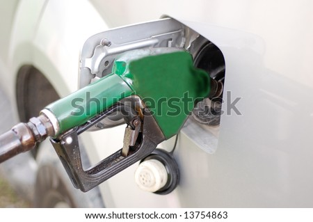 Green refueling hose inside a car's fuel tank - stock photo