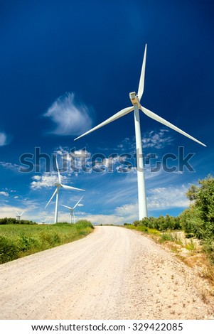 Green renewable energy concept - wind generator turbines in real landscape with grass and road, vertical - stock photo