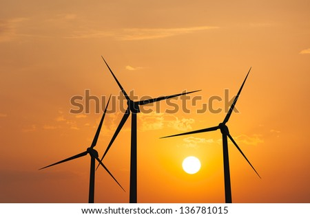 Green renewable energy concept - wind generator turbines in sky on sunset - stock photo