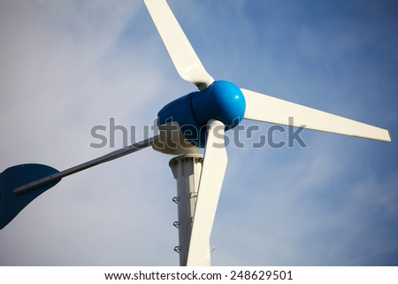Green renewable energy concept - wind generator turbines on blue sky background