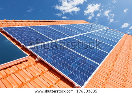 Green renewable energy with photovoltaic solar panels on roof - stock photo