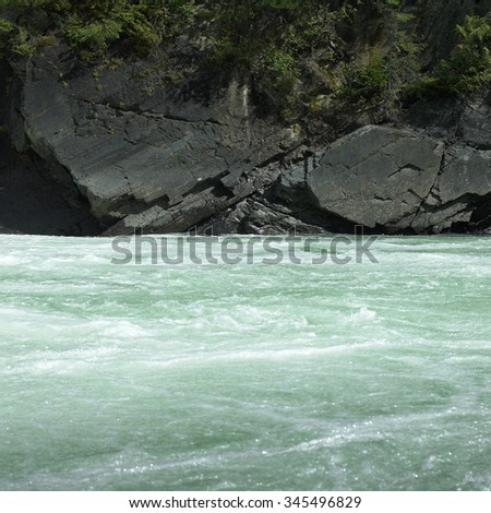 Green river water flowing near rocky edges - stock photo