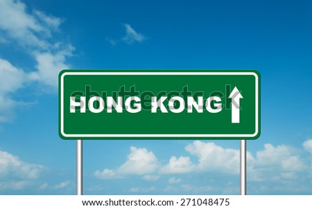 Green road sign board with straight direction to Hong Kong with sky background - stock photo