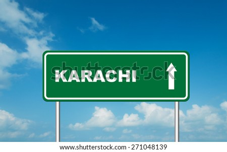 Green road sign board with straight direction to Karachi with sky background - stock photo