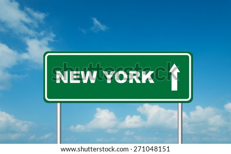 Green road sign board with straight direction to New York with sky background - stock photo
