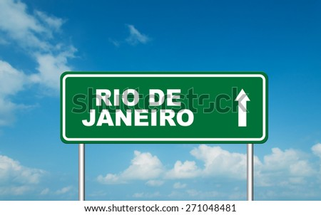 Green road sign board with straight direction to Rio De Janeiro with sky background - stock photo