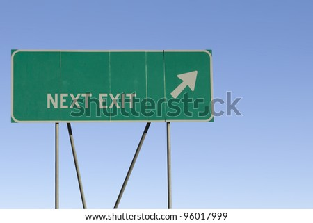 Green road sign with a blue sky gradient background. - stock photo