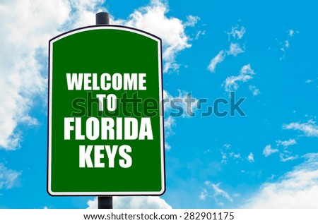 Green road sign with greeting message WELCOME TO FLORIDA KEYS isolated over clear blue sky background with available copy space. Travel destination concept  image - stock photo