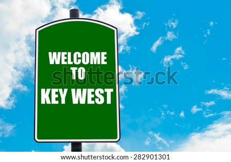 Green road sign with greeting message WELCOME TO KEY WEST isolated over clear blue sky background with available copy space. Travel destination concept  image - stock photo
