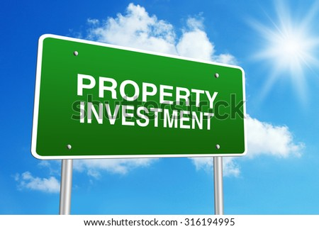 Green road sign with text Property investment is in front of the blue sunny background. - stock photo