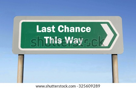 Green road sign with the message of a Last Chance This Way concept against a blue sky background - stock photo