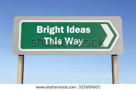 Green road sign with the message of Bright Ideas This Way concept against a blue sky background - stock photo