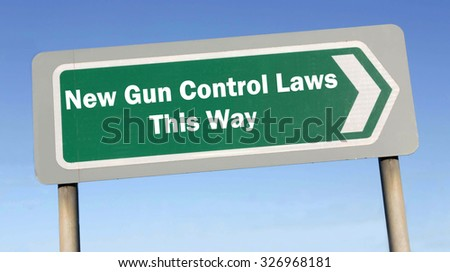 Green road sign with the message of New Gun Control Laws This Way concept against a blue sky background - stock photo
