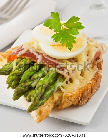 Green roasted asparagus, ham and cheese on toast