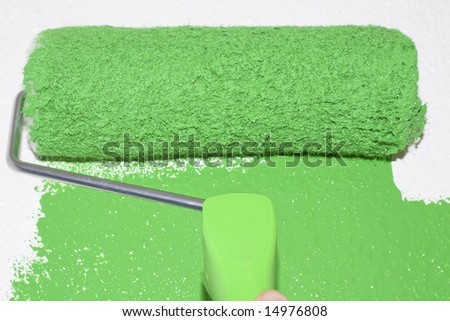 Green roller coloring white surface - stock photo
