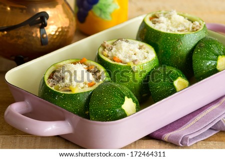 Green round zucchini stuffed with minced meat, vegetables, and cheese - stock photo