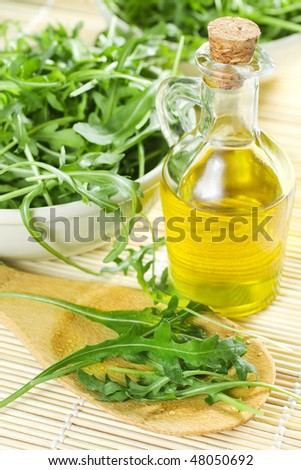 Green Rucola Salad And A Bottle Of Oil - stock photo