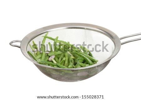 Green runner beans in a stainless steel sieve isolated against white