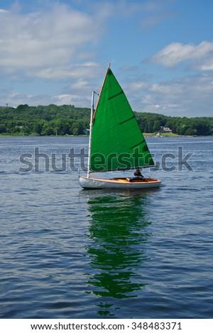 Green Sail Cat-Rig Sailboat - stock photo
