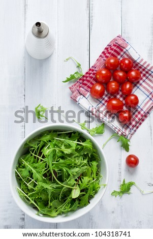 Green salad and cherry tomatoes on a white table - stock photo