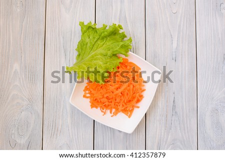 green salad leaf on plate with carrot. flat lay. top view - stock photo