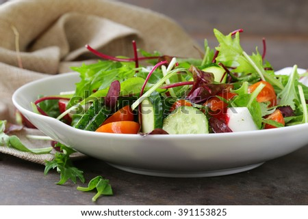 Green salad mix with fresh vegetables - cucumber, radish, tomato for healthy food diet - stock photo