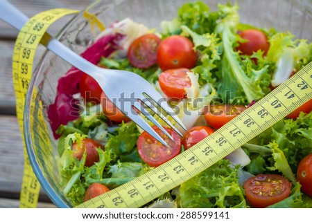 Green salad with a yellow measuring tape