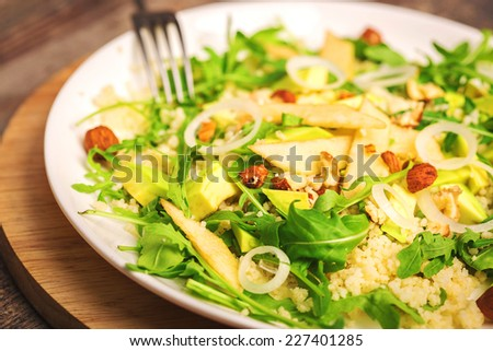 green salad with avocado rucola nuts and couscous vegetarian healthy food - stock photo